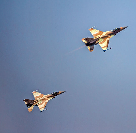 Low angle view of fighter planes flying against blue sky