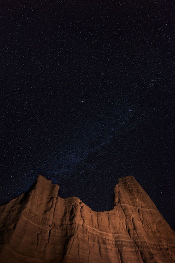 Low angle view of rock formations against sky at night