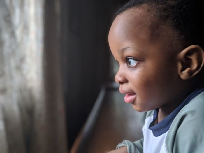 Profile view of thoughtful baby boy looking through window at home