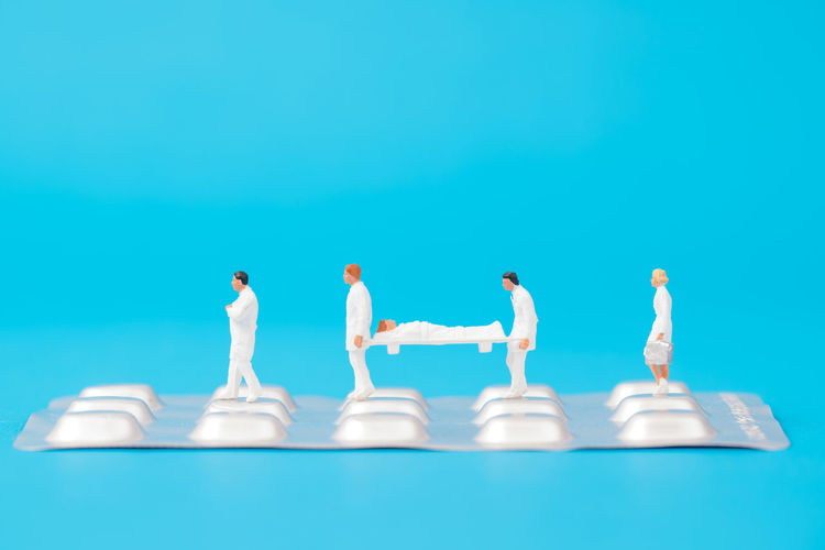 miniature people healthy team and medical drug,medical concept Doctor  Drug Hospital Medicine PainKiller Panel Teamwork Therapy Antibiotic Blue Background Figurine  Healthcare And Medicine Miniature People Patient Pill Small Treat