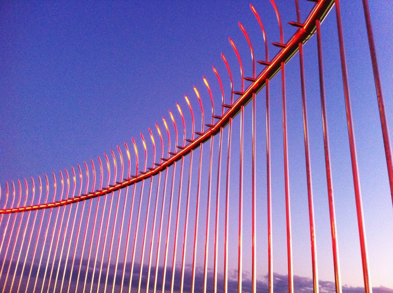 Low Angle View Of Metal Fence Against Sky At Dusk