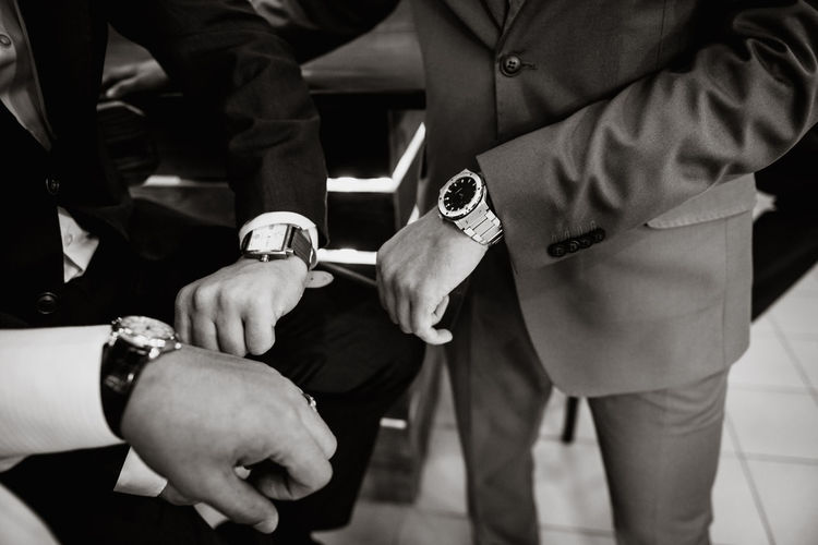 Midsection of businessmen showing wrist watches