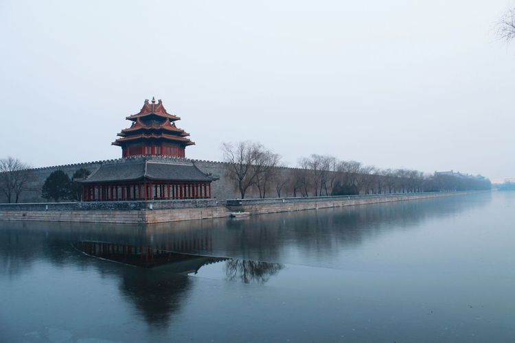 Temple by river against clear sky