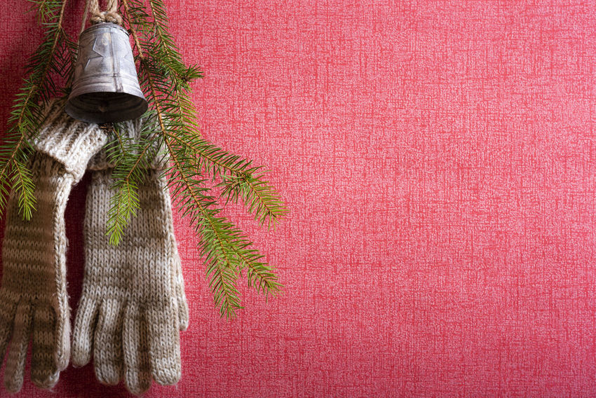 Hand gloves hanged with a nail on a red wall together with a pine tree twig and a christmas bell Bell Christmas Christmas Bell Childhood Cold Temperature Copy Space Decoration Domestic Room Hand Gloves Hanging Home Interior Indoors  Red Red Wall Textile Twig Winter Time
