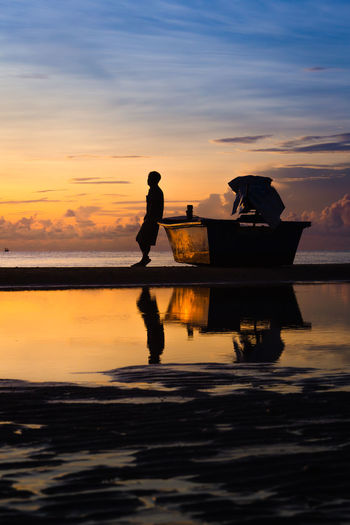A man leaning against a boat in the morning