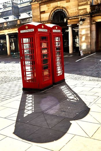 Iconic London phone boxes, casting shadows, in the morning sun. Shadow Shadows And Backlighting Phonebox Iconic Red Phonebox Iconiclondon