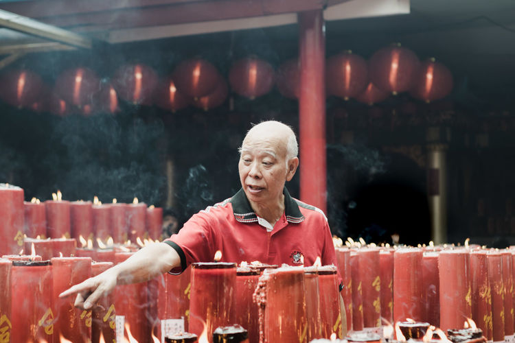 Man Pointing By Candles In Temple