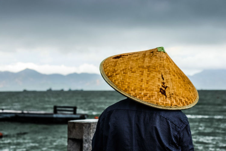 Rear view of men wearing asian style conical hat at beach against sky