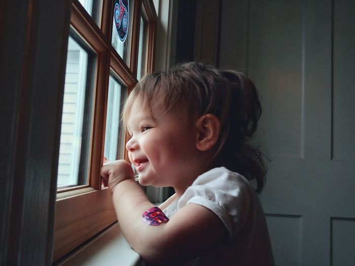 Side view of cute smiling baby girl looking through window at home