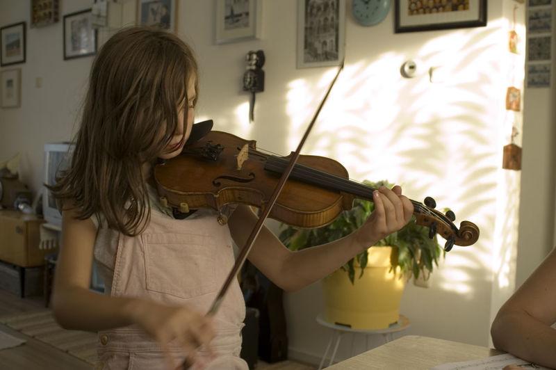 Girl Playing Violin At Home