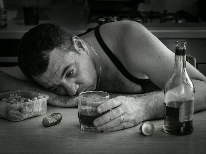 Close-up of man drinking whiskey on table