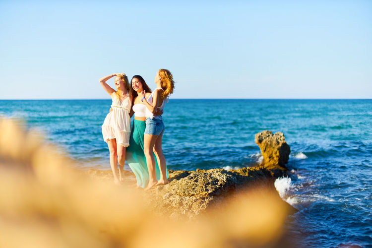 Happy female friends standing on rock by sea during sunny day