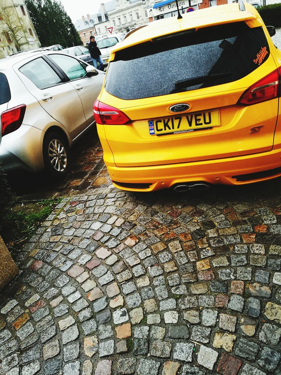 car, mode of transportation, transportation, motor vehicle, street, city, land vehicle, yellow, day, cobblestone, architecture, taxi, text, outdoors, no people, stone, road, footpath, built structure, paving stone