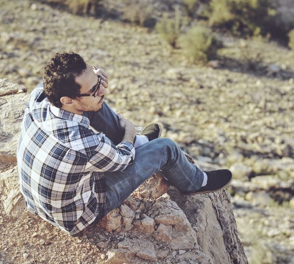Sitting on a rock in the desert Desert Riyadh Casual Clothing Contemplation Day Focus On Foreground Hairstyle Jeans Leisure Activity Lifestyles Men Nature One Person Outdoors Real People Relaxation Rock Rock - Object Side View Sitting Solid Young Adult Young Men