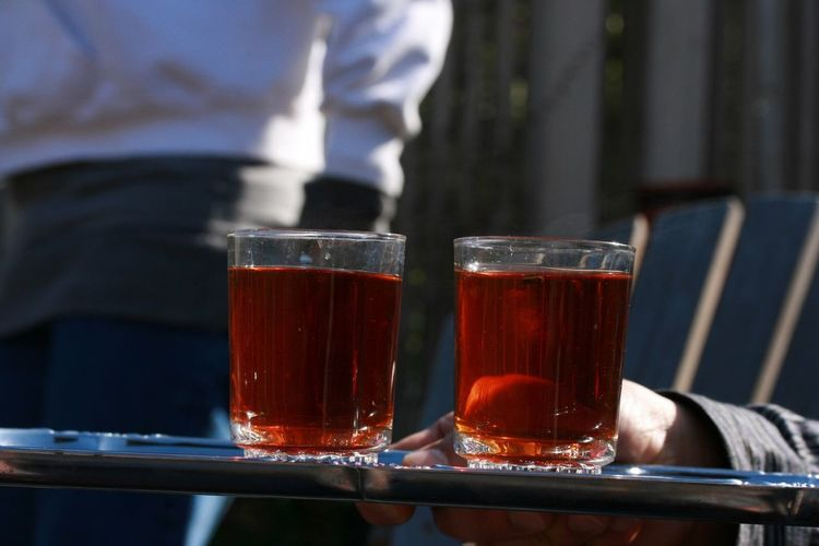 Cropped hand holding tea glasses on tray