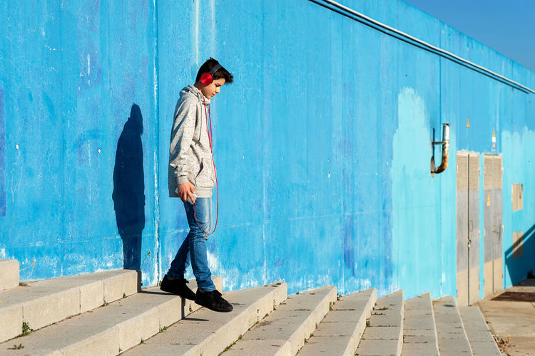 Man standing on footpath against blue wall