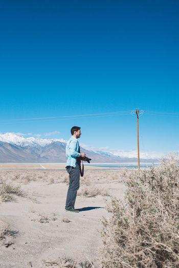 Full length of man standing on desert against clear blue sky
