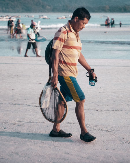 Full length of young man looking at camera on beach