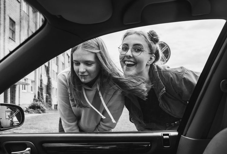 Portrait of 2 teenagers smiling against car window