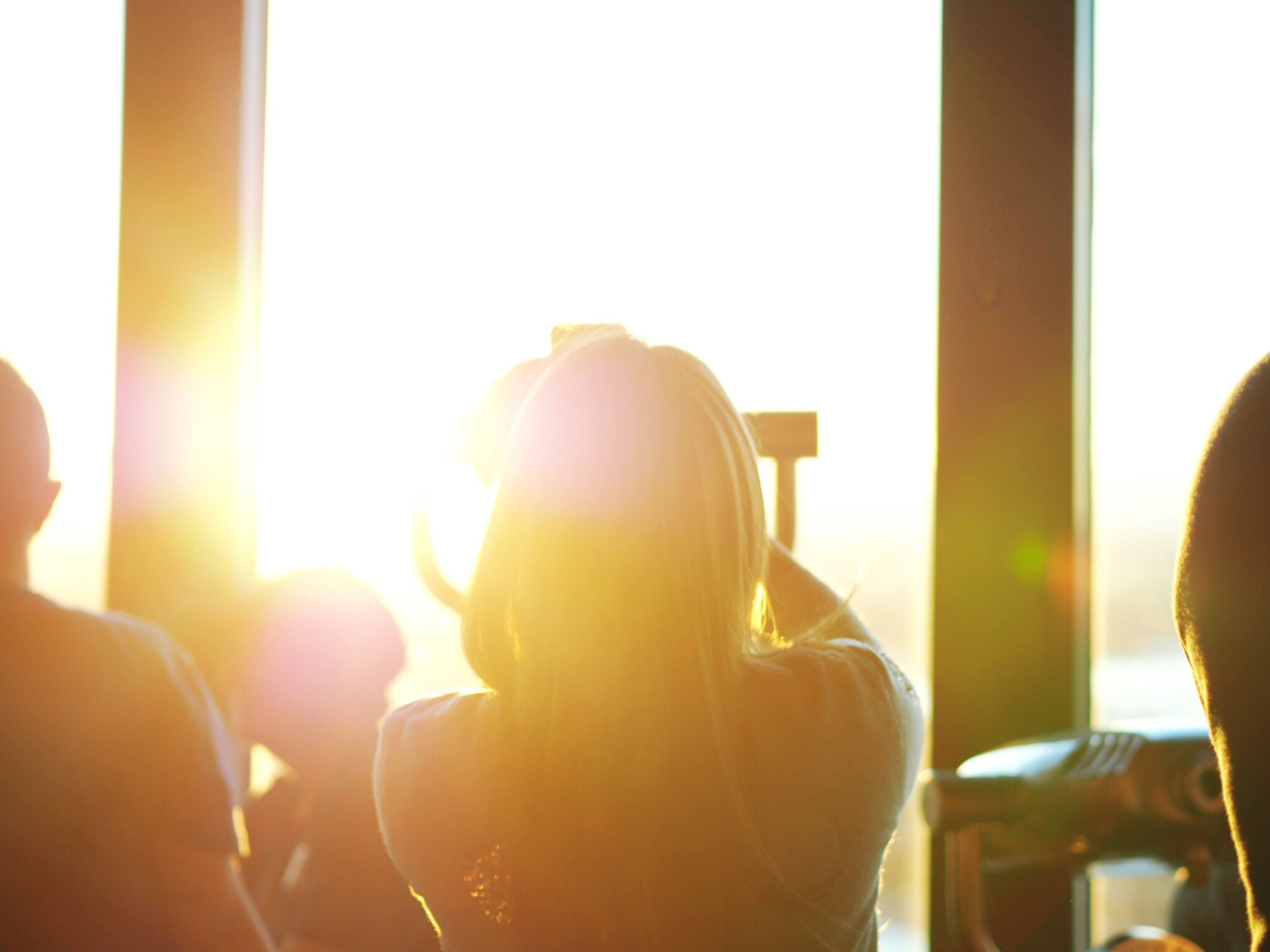 indoors, window, rear view, headshot, close-up, holding, back lit, person, day, focus on foreground, lens flare