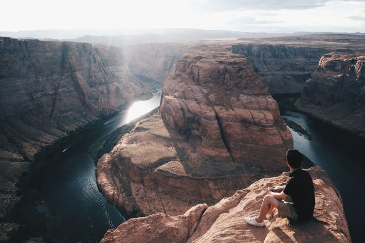 Man sitting on rock formations by horseshoe bend