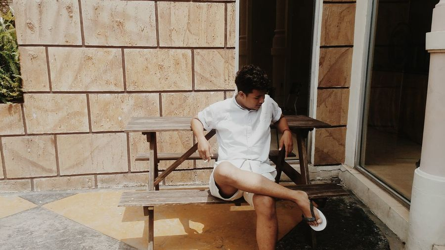 Young man sitting on bench outdoors