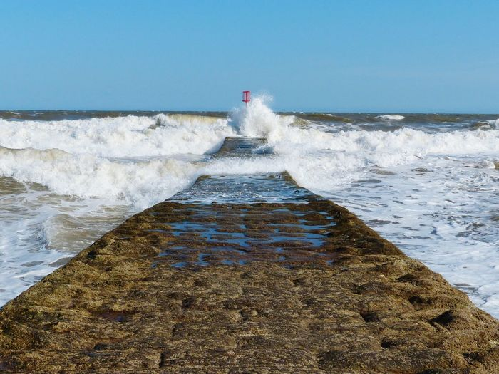 Waves Splashing On Pier Against Clear Sky