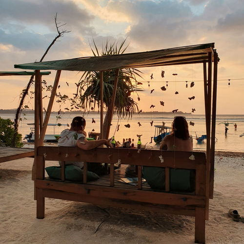 People sitting on table at beach during sunset