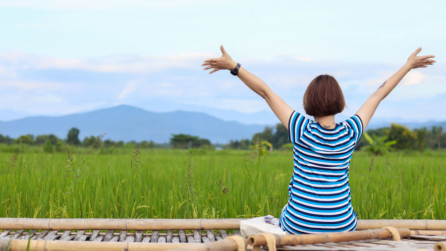 Rear view of woman with arms raised on field