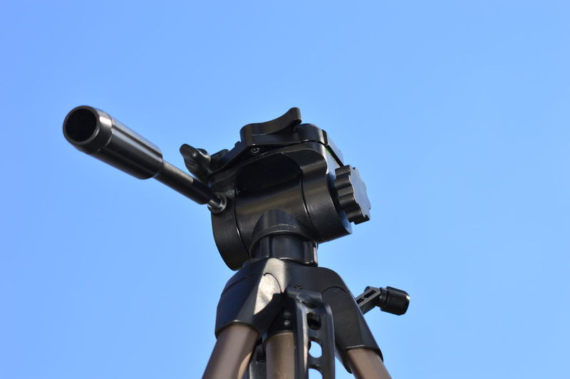 Low angle view of camera against clear blue sky