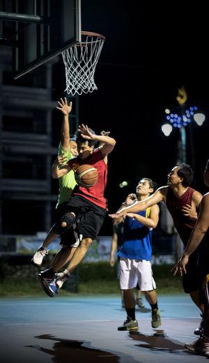 Men Playing Basketball In Court At Night