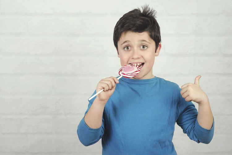 Boy Lollipop Eat Teeth Sugar Fun Funny Child Candies Confectionery Candy Childhood Thoughtful Expression Emotion Humor Happy Cavities Happiness Dessert Tasty Portrait Kid Lifestyle Nutrition Concept Sweet Food Eating Dentist Party Temptation Smile Nibble Face Cute Positive Smiling Innocence Standing