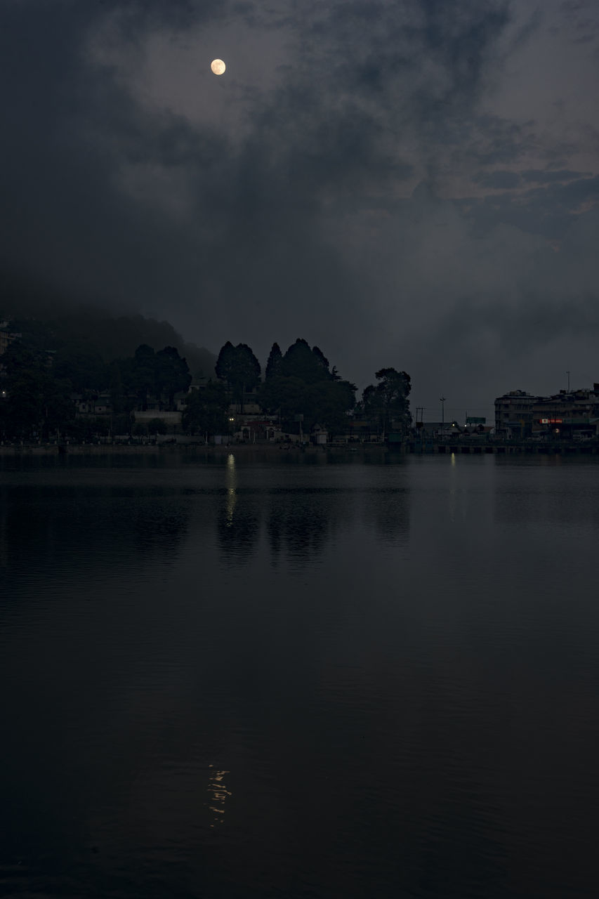 SCENIC VIEW OF RIVER BY ILLUMINATED BUILDINGS AGAINST SKY