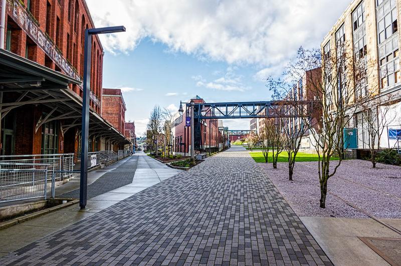 Walkway In City Against Sky