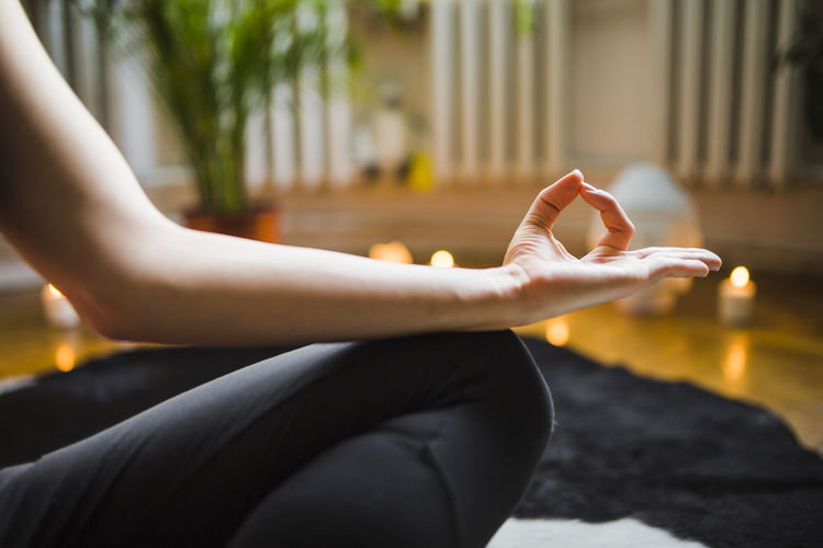 Midsection of woman exercising at home