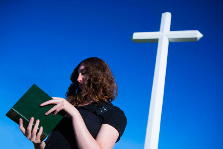 Low angle view of woman reading book against blue sky