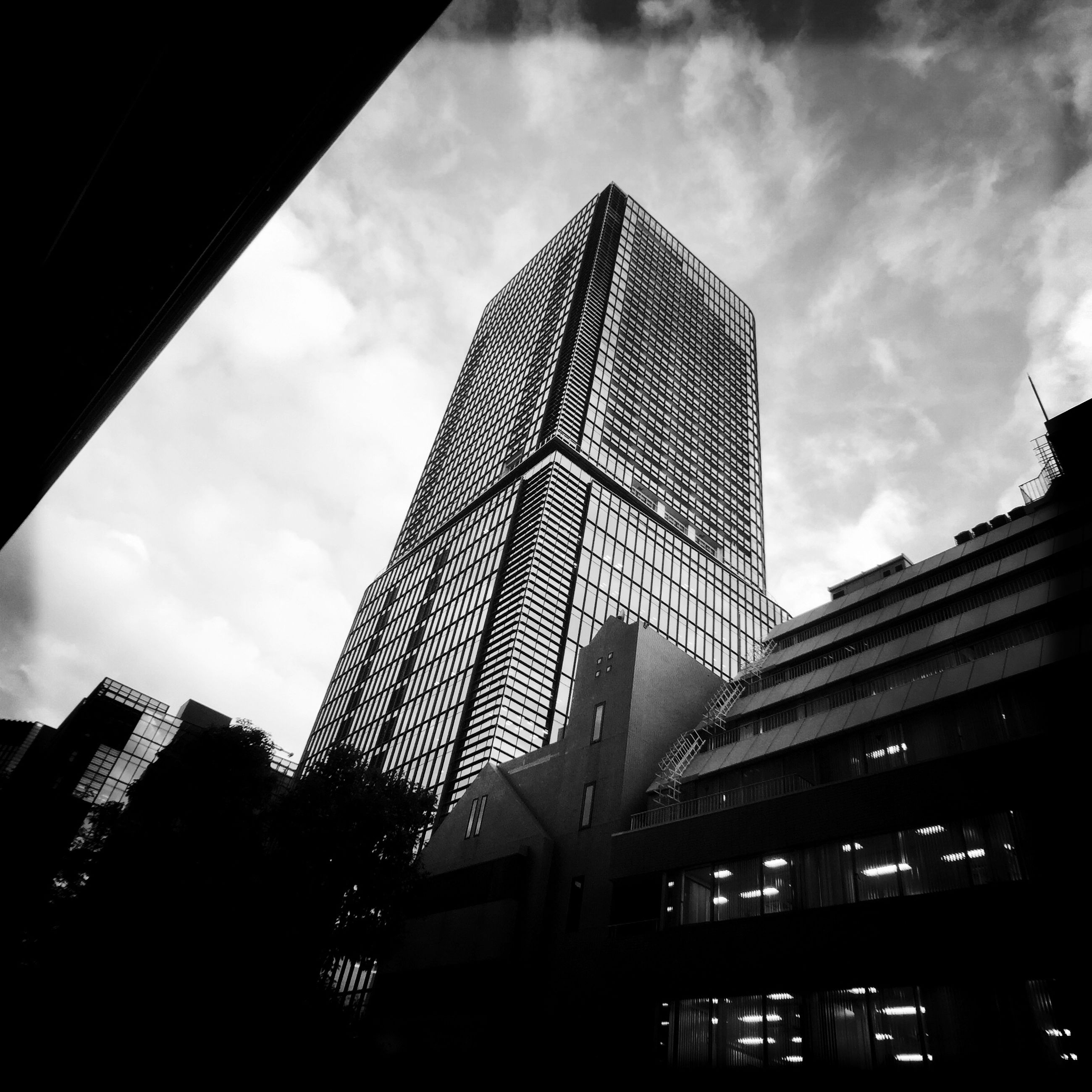 architecture, building exterior, built structure, low angle view, skyscraper, city, modern, office building, tall - high, sky, tower, building, cloud - sky, glass - material, city life, tall, cloud, no people, outdoors, residential building