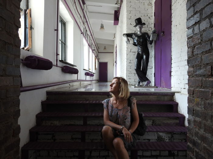 Woman looking up while sitting on steps