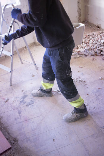 Low section of man working on floor