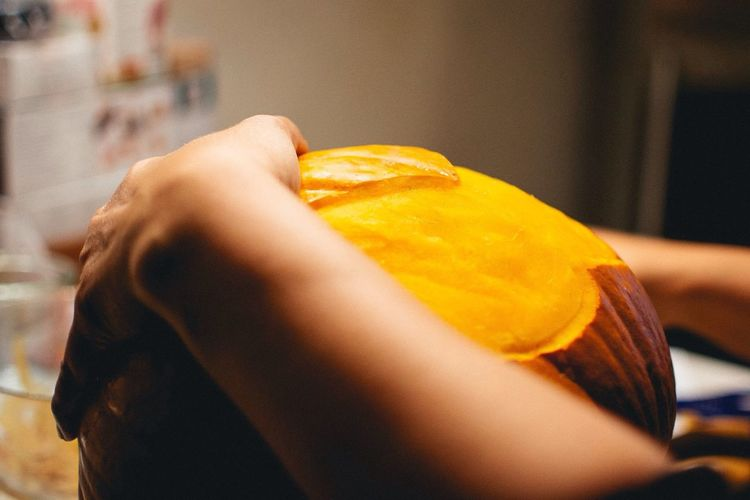 Cropped Image Of Boy Holding Jack O Lantern At Home
