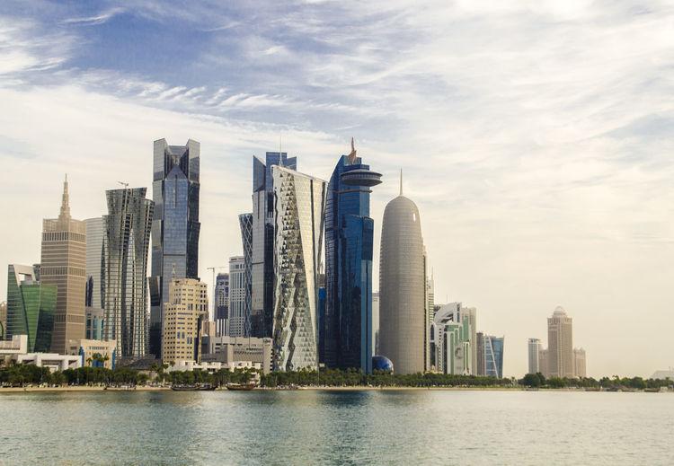 Skyscrapers By River Against Buildings In City Against Sky
