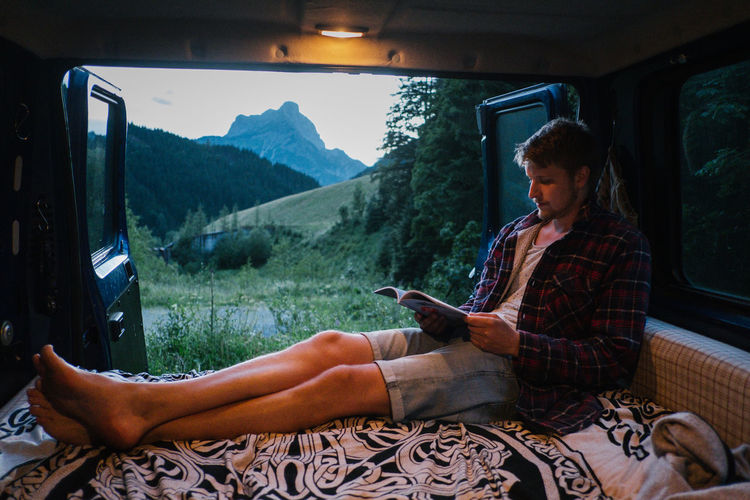 Young Man Reading Book In Motor Home