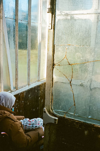 Low section of man sitting by window