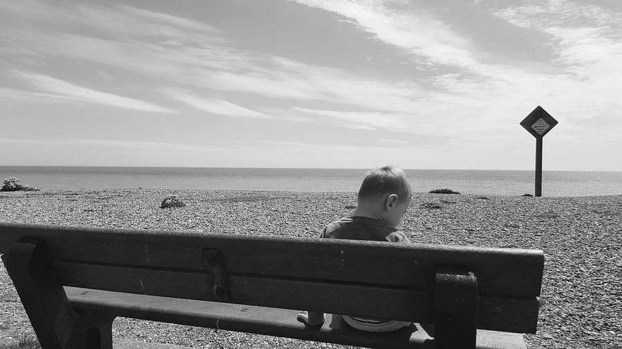Rear View Of Boy Sitting On Bench At Beach Against Sky During Sunny Day