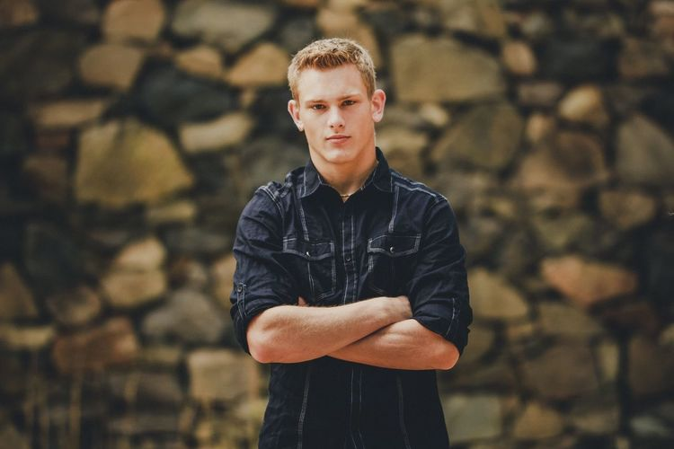 Portrait Of Young Man With Arms Crossed Standing Against Wall