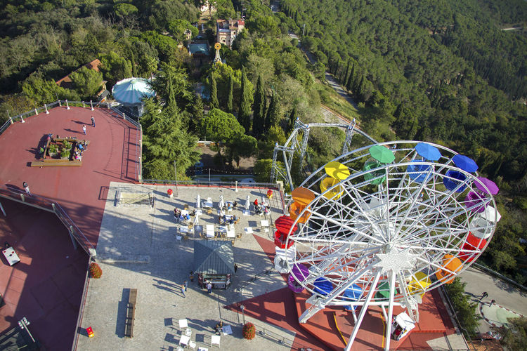 Amusement Park Ride Arts Culture And Entertainment Attraction Barcelona City Life Day Ferris Wheel Fun Green Color Leisure Activity Multi Colored Outdoors Park Society From Above Summer Summer Views Sunny Day Tibidabo Tourism Travel Destinations Wheel A Bird's Eye View