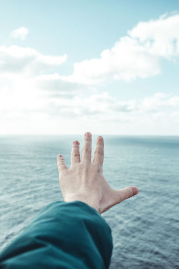 Midsection of person in sea against sky