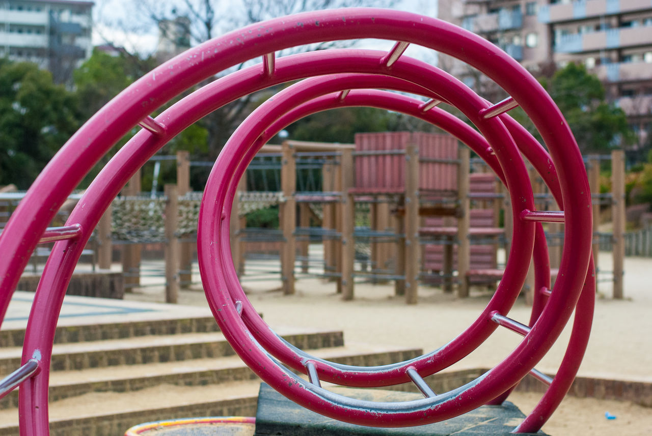 focus on foreground, day, metal, playground, no people, shape, red, architecture, built structure, close-up, jungle gym, outdoor play equipment, park, design, geometric shape, pink color, circle, city, building exterior, nature