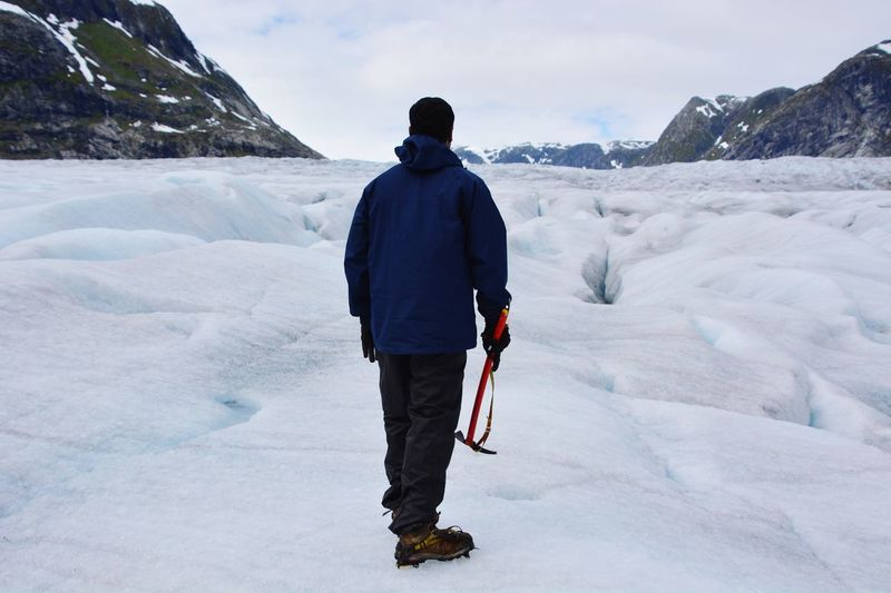 Rear View Of Man Standing With Axe At Glacier Against Sky
