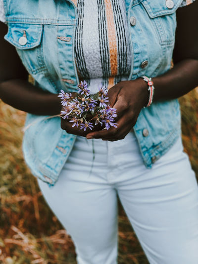 Midsection of woman holding flower in field